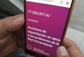 Manos sosteniendo un celular con la página institucional